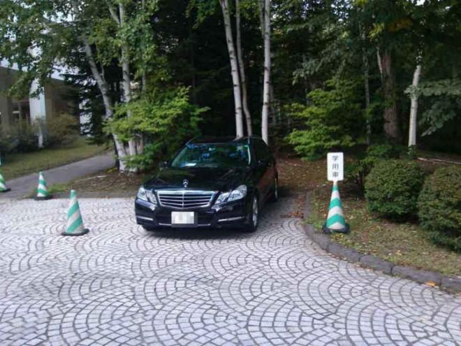 静かなキャンパスの専用駐車場にたたずむ高級車