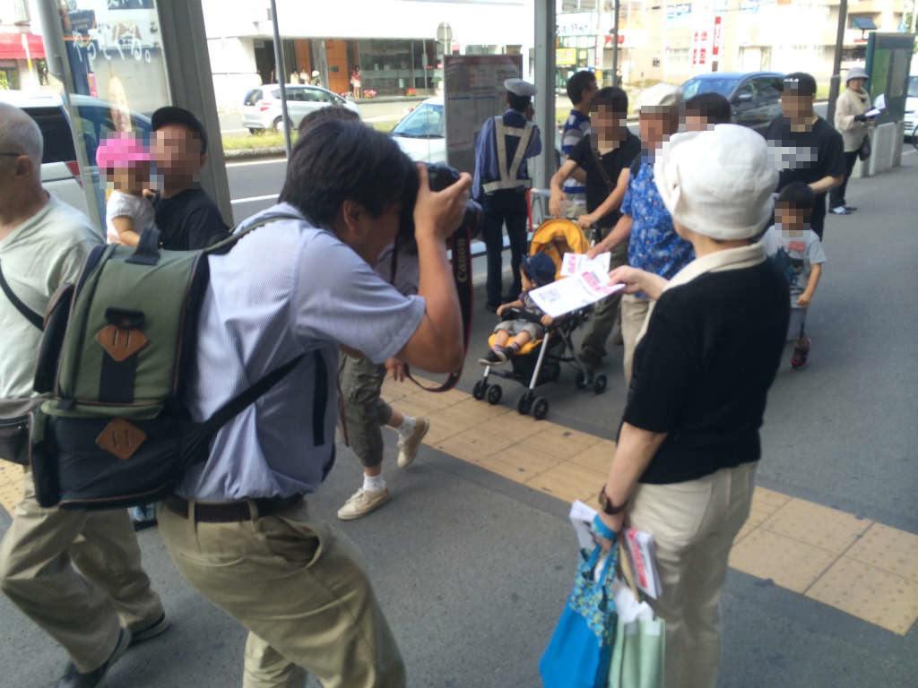 ビラ配りの活動家に中腰でカメラを向けるのは北海道新聞記者